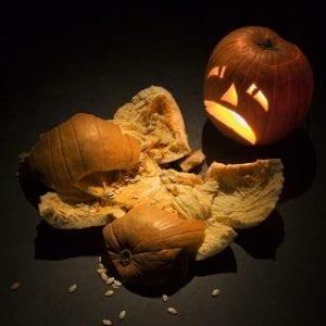 Upset jack-o'-lantern looking at smashed pumpkin.