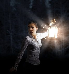 Young pretty businesswoman with lantern in darkness